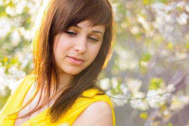 Jong meisje in gele kleding in de lente op kersenbloesem