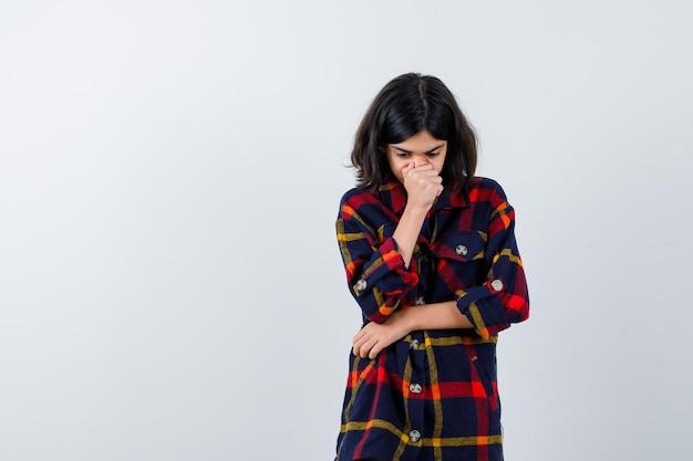 Jong meisje in geruit hemd dat mond en neus bedekt met hand terwijl ze de hand op de elleboog houdt en peinzend kijkt, vooraanzicht.