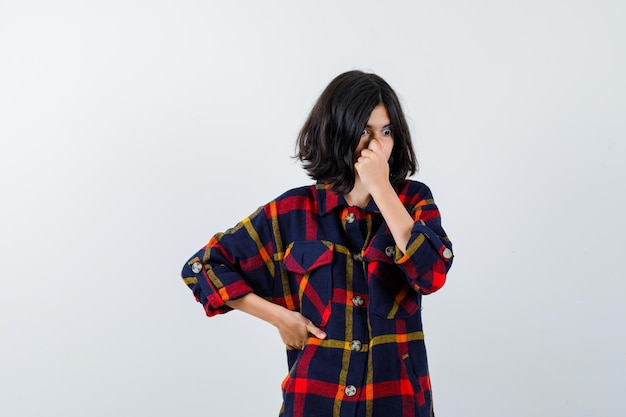 Jong meisje in geruit hemd dat neus knijpt vanwege een slechte geur terwijl ze de hand op de taille houdt en er gehaast uitziet, vooraanzicht.