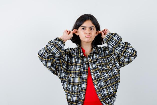 Jong meisje in geruit hemd en rood t-shirt die oren met vingers uitrekt en er serieus uitziet, vooraanzicht.