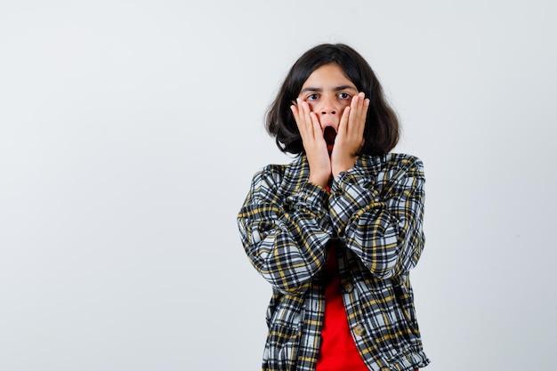 Jong meisje in geruit hemd en rood t-shirt hand in hand op wangen en verbaasd kijken, vooraanzicht.