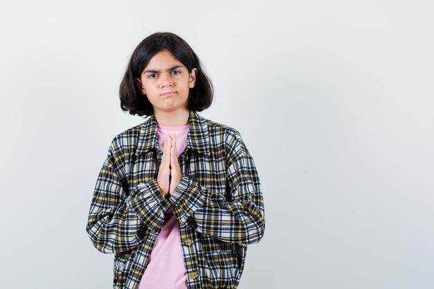 Jong meisje in geruit hemd en roze t-shirt handen in gebedspositie omklemd en heel serieus kijkend, vooraanzicht.