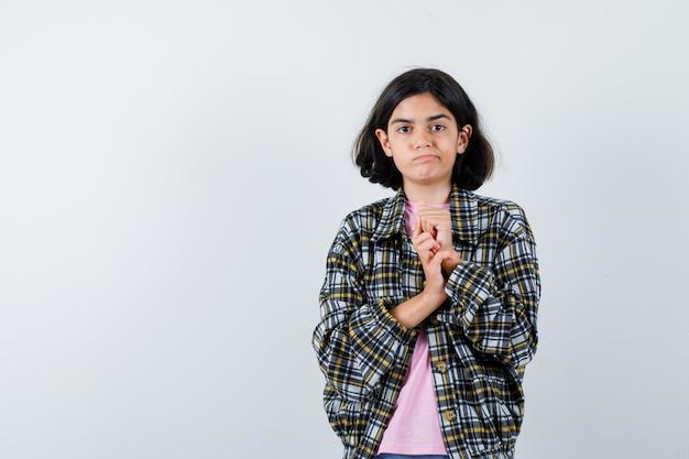 Jong meisje in geruit hemd en roze t-shirt handen vast en ziet er mooi uit, vooraanzicht.
