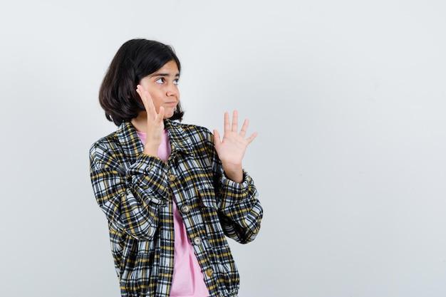 Jong meisje in geruit hemd en roze t-shirt met een hand in de buurt van het gezicht terwijl ze een stopbord toont en er gefocust uitziet, vooraanzicht.