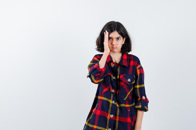 Jong meisje in geruit hemd hand in de buurt van gezicht en er serieus uitzien, vooraanzicht.
