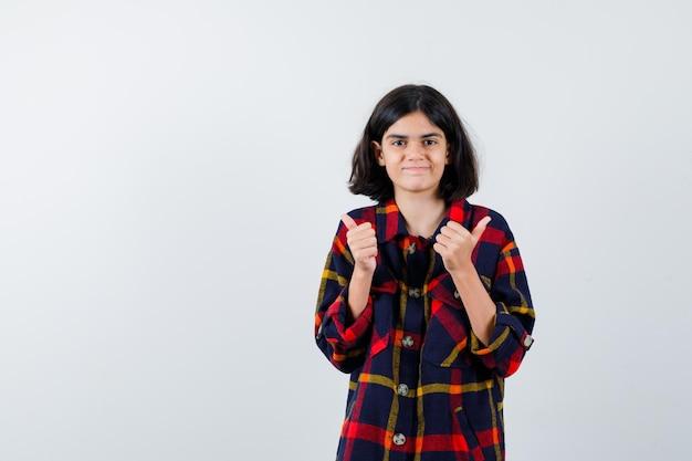 Jong meisje in geruit hemd met duimen naar beneden met beide handen en er gelukkig uit, vooraanzicht.