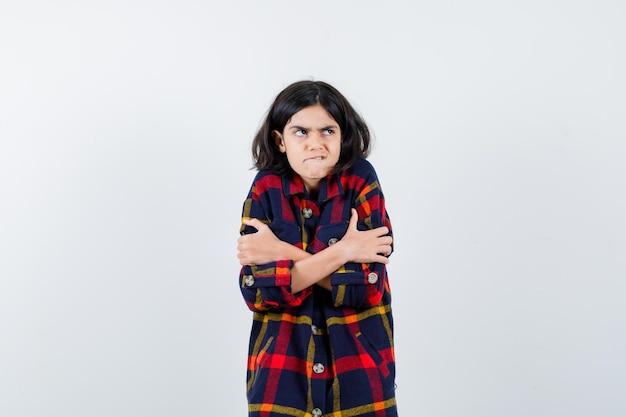 Jong meisje in geruit hemd rillend van de kou, bijtende lippen en gehaast, vooraanzicht.