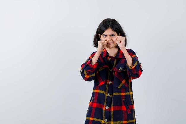 Jong meisje in geruit hemd staat in bokser pose en kijkt woedend, vooraanzicht.