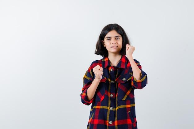 Jong meisje in geruit hemd staat in bokser pose en ziet er krachtig uit, vooraanzicht.
