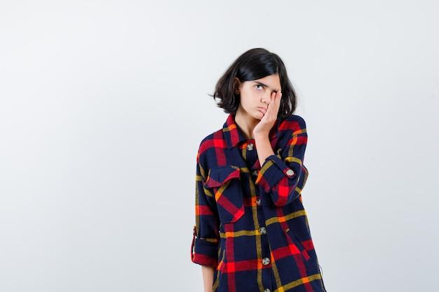 Jong meisje in geruit overhemd dat één oog bedekt en er schattig uitziet, vooraanzicht.