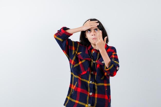 Jong meisje in geruit overhemd dat omhoog wijst terwijl ze de hand op het voorhoofd houdt en peinzend kijkt, vooraanzicht.