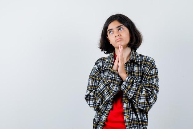 Jong meisje in geruit overhemd en rood t-shirt bidden en kijken serieus, vooraanzicht.