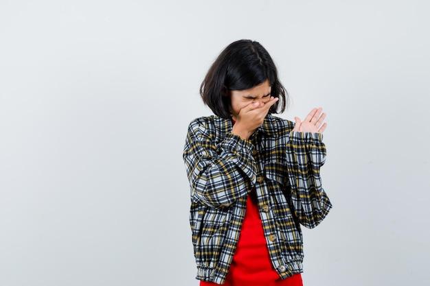 Jong meisje in geruit overhemd en rood t-shirt hand op mond zetten, niezen en serieus kijken, vooraanzicht.