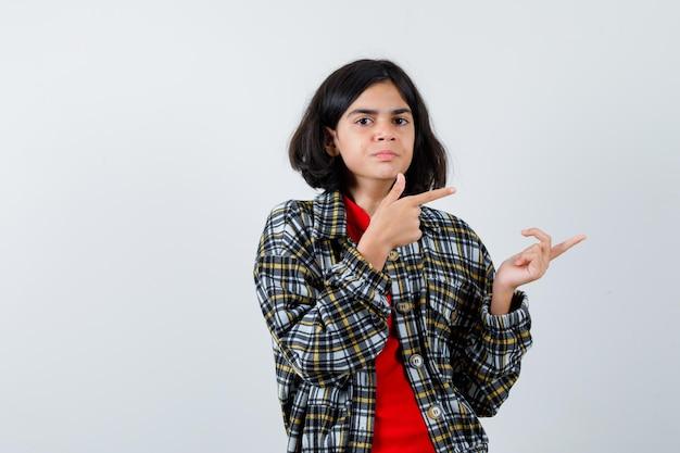Jong meisje in geruit overhemd en rood t-shirt naar rechts wijzend met wijsvingers en serieus kijkend, vooraanzicht.