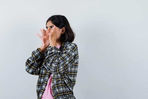 Jong meisje in geruit overhemd en roze t-shirt hand in hand in de buurt van mond als iemand bellen en gefocust kijken, vooraanzicht.