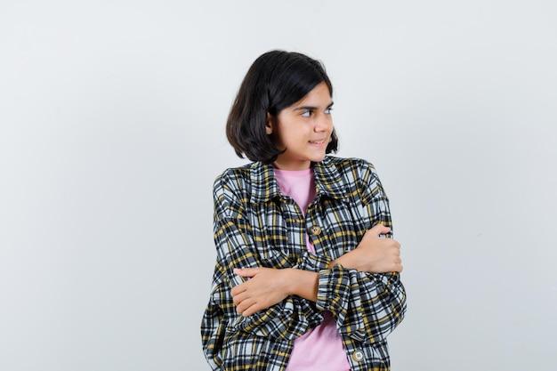Jong meisje in geruit overhemd en roze t-shirt staande armen gekruist, wegkijkend en gefocust, vooraanzicht.
