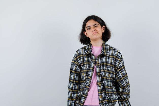 Jong meisje in geruit overhemd en roze t-shirt staat rechtop, knipoogt en poseert voor de camera en ziet er mooi uit, vooraanzicht.