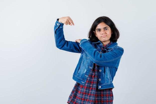 Jong meisje in geruit overhemd en spijkerjasje dat spieren toont en er krachtig uitziet, vooraanzicht.