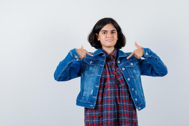 Jong meisje in geruit overhemd en spijkerjasje wijzend naar zichzelf met wijsvingers en schattig, vooraanzicht.