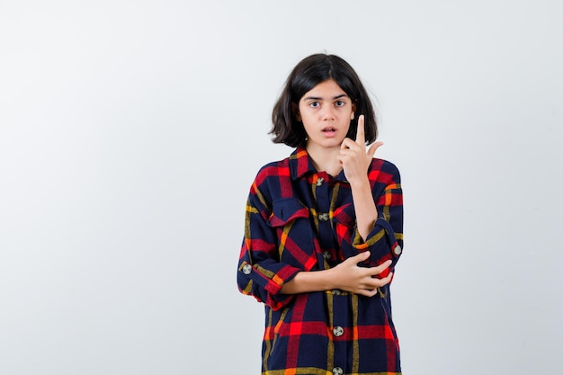 Jong meisje in geruit overhemd met wijsvinger in eureka-gebaar terwijl ze de hand op de elleboog houdt en er verstandig uitziet, vooraanzicht.