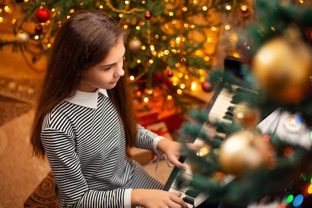 Jong meisje in gestreepte jurk die kerstliedjes speelt op de piano. feestelijke heldere vakantiedecoratie op de achtergrond.