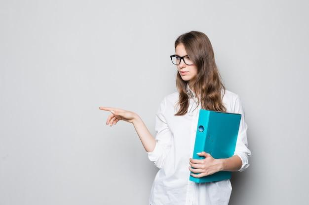 Jong meisje in glazen gekleed in strikte kantoor wit t-shirt staat voor witte muur met blauwe map voor documenten in haar handen