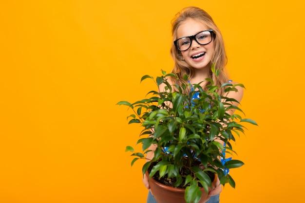 Jong meisje in glazen heeft een pot met een plant en een gieter op een oranje muur