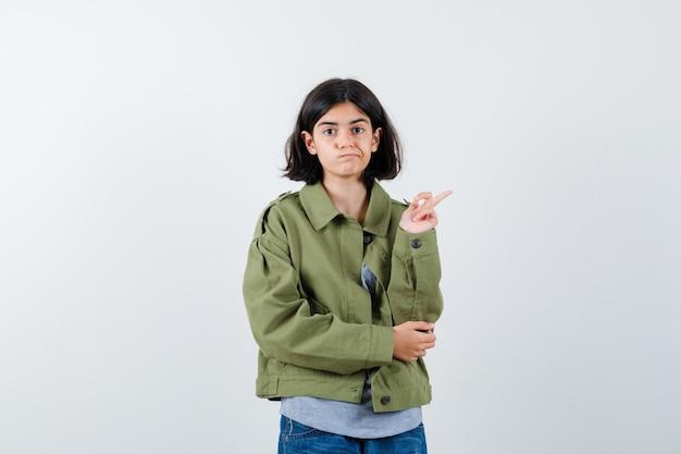 Jong meisje in grijze trui, kaki jas, jeansbroek die naar rechts wijst terwijl ze de hand op de elleboog houdt en er schattig uitziet, vooraanzicht.