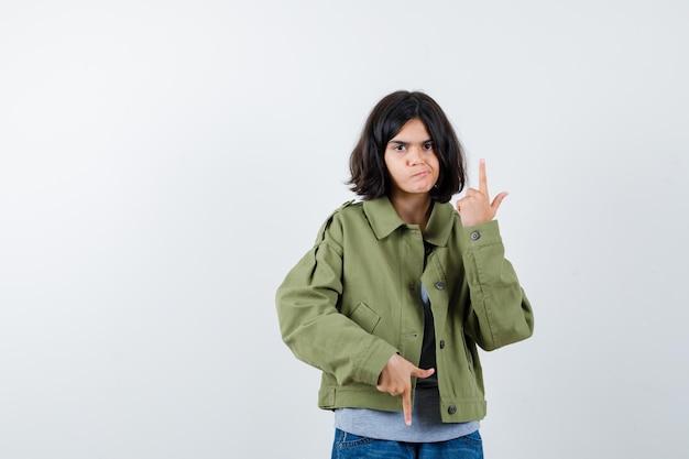 Jong meisje in grijze trui, kaki jas, jeansbroek die op en neer wijst en er serieus uitziet, vooraanzicht.