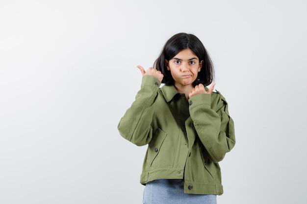 Jong meisje in grijze trui, kaki jasje, jeansbroek die duimen met beide handen toont en er gelukkig uitziet, vooraanzicht.