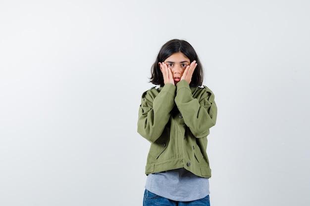 Jong meisje in grijze trui, kaki jasje, jeansbroek die handen op de wangen houdt en verrast kijkt, vooraanzicht.