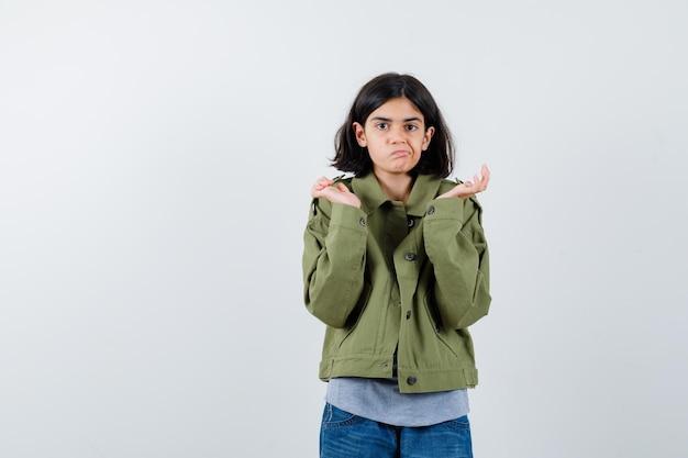 Jong meisje in grijze trui, kaki jasje, jeansbroek die handen op vragende manier uitrekt en verbaasd kijkt, vooraanzicht.