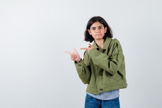 Jong meisje in grijze trui, kaki jasje, jeansbroek die met wijsvingers naar links wijst en er serieus uitziet, vooraanzicht.