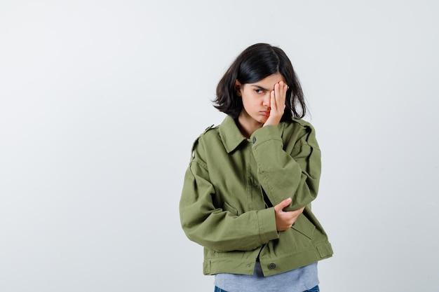 Jong meisje in grijze trui, kaki jasje, jeansbroek die oog met hand bedekt, hand op elleboog houdt en peinzend kijkt, vooraanzicht.