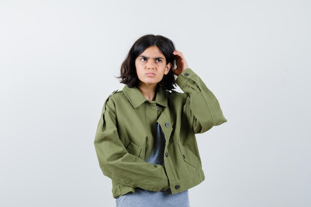 Jong meisje in grijze trui, kaki jasje, jeansbroek die op het hoofd krabt, wegkijkt en peinzend kijkt, vooraanzicht.