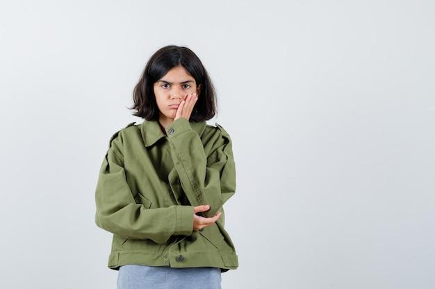 Jong meisje in grijze trui, kaki jasje, jeansbroek leunend op de handpalm terwijl ze aan iets denkt en peinzend kijkt, vooraanzicht.