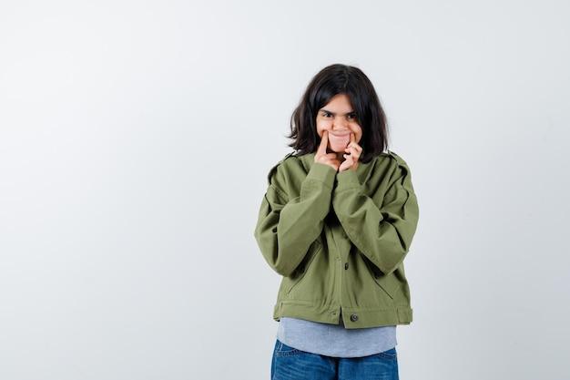 Jong meisje in grijze trui, kaki jasje, jeansbroek met wijsvingers in de buurt van mond, dwingt een glimlach en ziet er schattig uit, vooraanzicht.