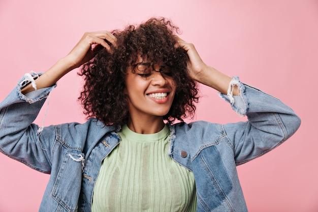 Jong meisje in groen t-shirt glimlacht en danst op roze muur. coole vrouw raakt haar krullende haar aan