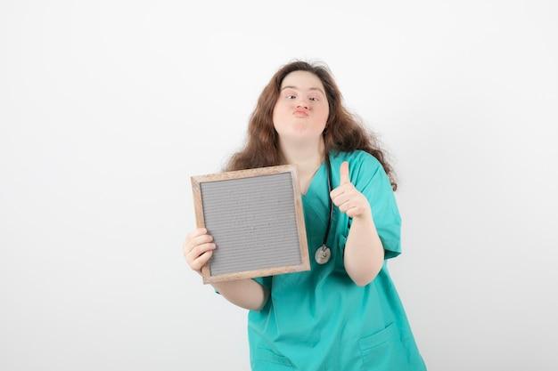 Jong meisje in groen uniform met een frame met een duim omhoog. vrouw