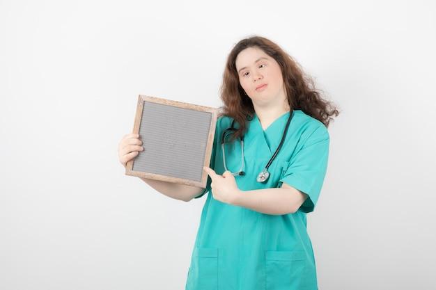 Jong meisje in groen uniform wijzend op een frame.