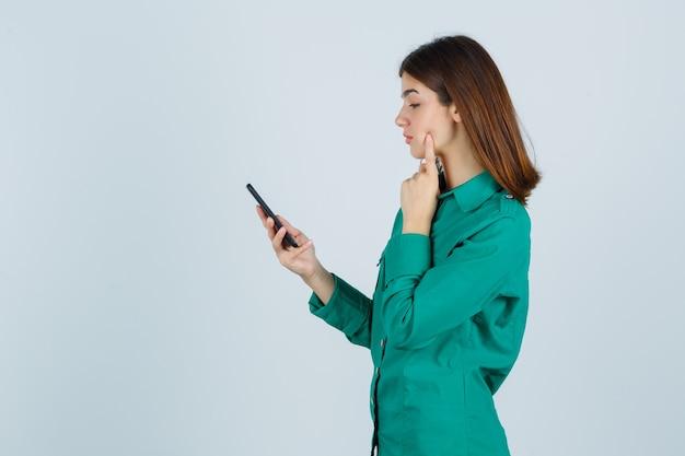Jong meisje in groene blouse, zwarte broek die berichten op telefoon leest, wijsvinger op wang zet en gericht, vooraanzicht kijkt.