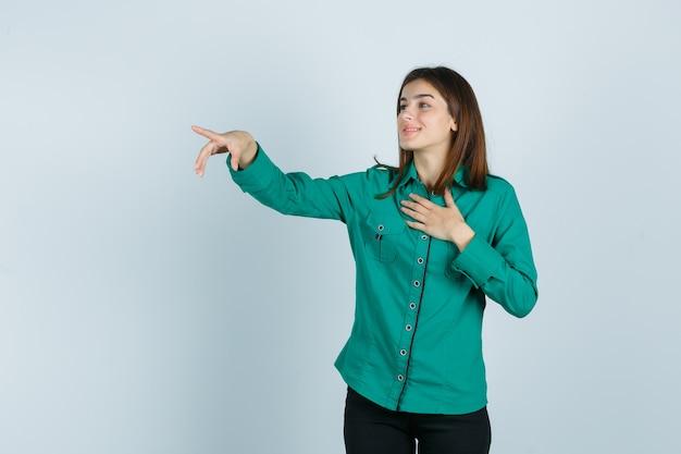 Jong meisje in groene blouse, zwarte broek die één hand over borst houdt, met wijsvinger weg wijst en gelukkig, vooraanzicht kijkt.