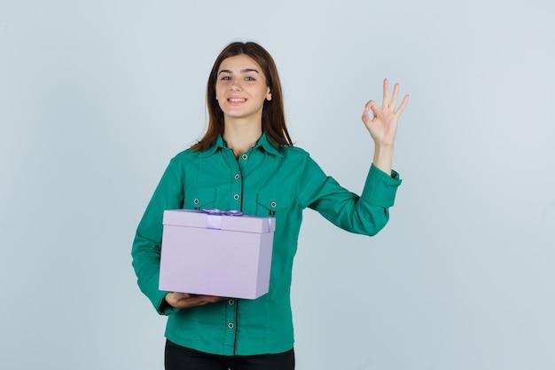 Jong meisje in groene blouse, zwarte broek die giftdoos houdt, ok teken toont en vrolijk, vooraanzicht kijkt.