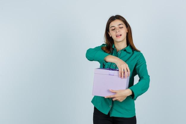 Jong meisje in groene blouse, zwarte broek die giftdoos probeert te openen en gelukkig, vooraanzicht kijkt.