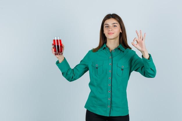 Jong meisje in groene blouse, zwarte broek die glas rode vloeistof houdt, ok teken toont en gelukkig, vooraanzicht kijkt.
