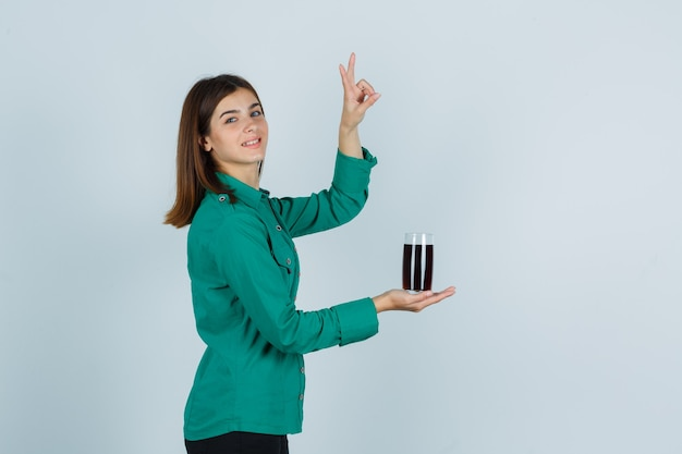 Jong meisje in groene blouse, zwarte broek die glas zwarte vloeistof houdt, vredesgebaar toont en gelukkig, vooraanzicht kijkt.