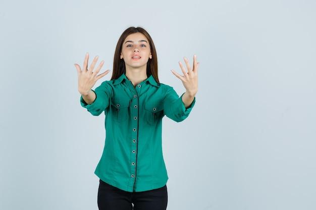 Jong meisje in groene blouse, zwarte broek die handen uitrekt als iets denkbeeldigs vasthoudt en er gelukkig uitziet, vooraanzicht.