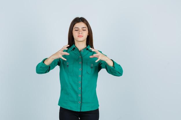 Jong meisje in groene blouse, zwarte broek die handen uitrekt als iets denkbeeldigs vasthoudt en gericht, vooraanzicht kijkt.