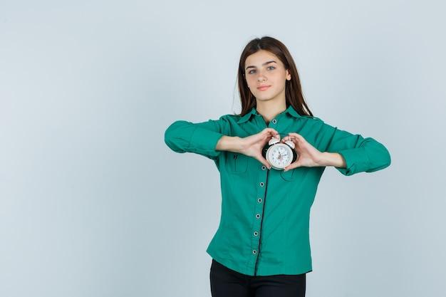 Jong meisje in groene blouse, zwarte broek die klok in beide handen houdt en gelukkig, vooraanzicht kijkt.