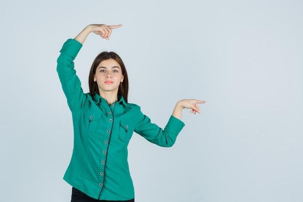 Jong meisje in groene blouse, zwarte broek die met wijsvingers naar rechts wijst en er gelukkig uitziet, vooraanzicht.